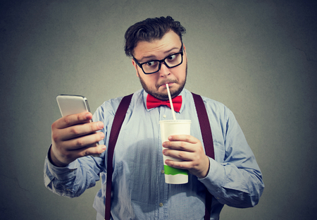 Photo pour Young chubby man addicted to social media and network using phone and drinking sweet soda.  - image libre de droit