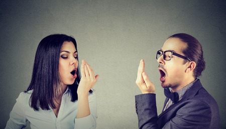 Photo pour Young couple woman and man checking their breath with hand gesture  - image libre de droit