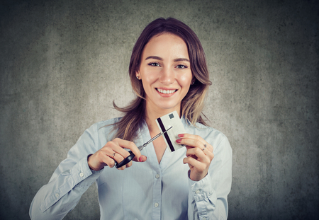 Photo pour Cheerful young business woman looking happily at camera done with credit cards.  - image libre de droit