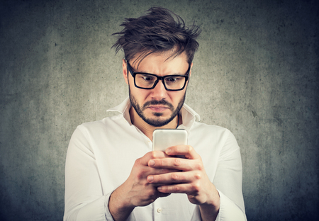 Photo pour stunned man, surprised offended, shocked by what he sees on his smartphone - image libre de droit