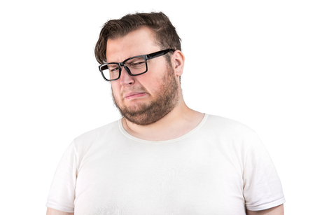 Foto de Young bearded man in glasses frowning of bad smell looking deeply displeased on white background - Imagen libre de derechos