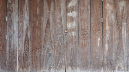Wooden vintage, retro folding door is close brown color tone background the country shop has key lock at Thailand.