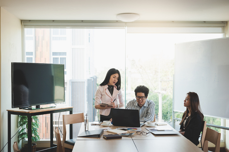 Foto de Young Asian businessman and businesswoman talking about their work in meeting room. Business team discussion planning and brainstorm in office conept. - Imagen libre de derechos