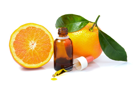 Foto de Orange with green leaves and a bottle with dropper isolated on a white - Imagen libre de derechos