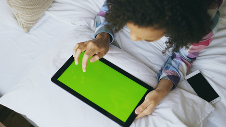 Photo pour Top view of curly mixed race woman lying in bed at home using electronic tablet with green screen - image libre de droit