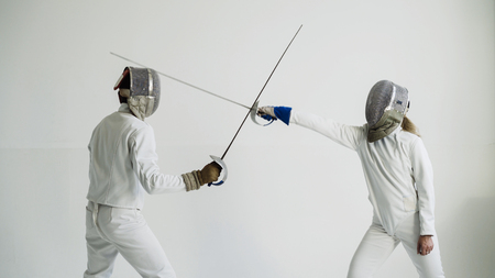 Foto de Young woman fencer having fencing training with trainer in white studio indoors - Imagen libre de derechos