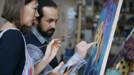 Foto de Skilled artist teacher showing and discussing basics of painting to student at art-class - Imagen libre de derechos