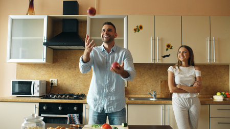 Photo for Attractive loving couple having fun in the kitchen. Handsome man juggle with apples to impress his girlfriend - Royalty Free Image