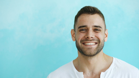 Photo pour Closeup portrait of young smiling and laughing man looking into camera on blue background - image libre de droit