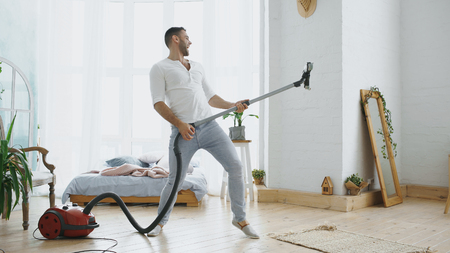 Foto de Young man having fun cleaning house with vacuum cleaner dancing like guitarist - Imagen libre de derechos