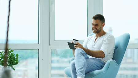 Photo for Young smiling man doing online shopping using digital tablet computer sitting at balcony in modern loft apartment - Royalty Free Image