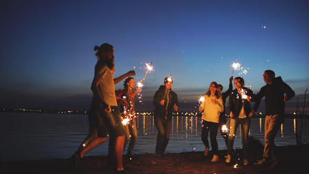 Photo pour Group of young friends having a beach party. Friends dancing and celebrating with sparklers in twilight sunset - image libre de droit