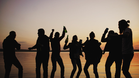Photo for Silhouette of Group young dancing people have a party at beach on sunset - Royalty Free Image
