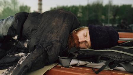 Foto de Young Homeless man trying to sleep under jacket on bench at the sidewalk - Imagen libre de derechos