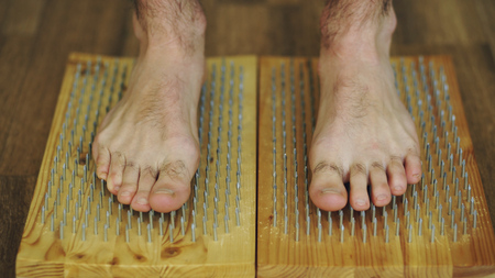 Photo pour Closeup of yoga man stand on the board with sharp nails - image libre de droit