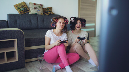 Photo pour Two funny women play console games with gamepad and have fun at home - image libre de droit