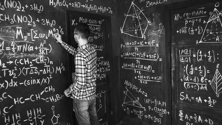 Foto de Young scientist man write chock in chemical and mathematical equations wall room interior - Imagen libre de derechos
