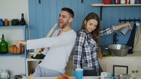 Foto de Young joyful couple have fun dancing and singing while set the table for breakfast in the kitchen at home - Imagen libre de derechos