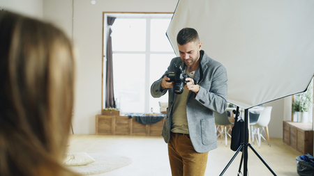 Photo for Professional photographer taking photos of model on digital camera working in photo studio - Royalty Free Image