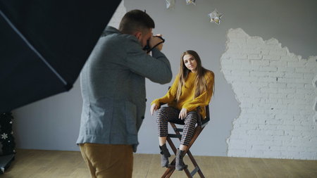 Photo for Young beautiful woman model posing for photographer while he is shooting with a digital camera in photo studio indoors - Royalty Free Image