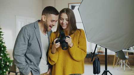 Photo for Professional photographer woman showing photos on digital camera to attractive model man in photo studio indoors - Royalty Free Image