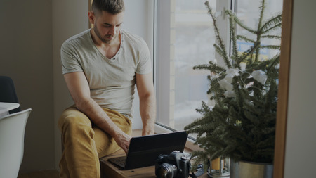 Photo pour Concentrated male photographer with camera and laptop computer sitting on windowsill at home and sharing her photos to social media - image libre de droit
