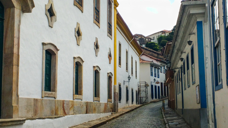 Photo pour March 25, 2016, historic city of Ouro Preto, Minas Gerais, Brazil, side view of stone pavement street with old houses and church. - image libre de droit