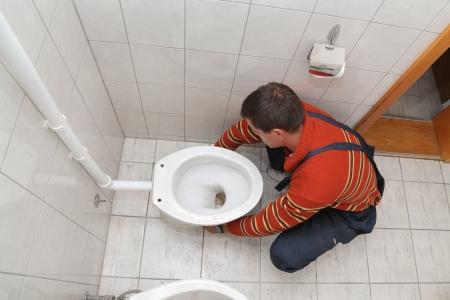 Plumber replacing broken toilet in a washroom