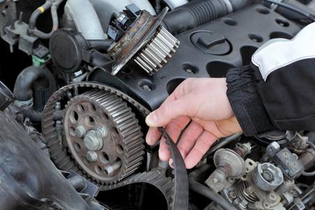 Photo pour Car mechanic replacing timing belt at camshaft of modern engine - image libre de droit