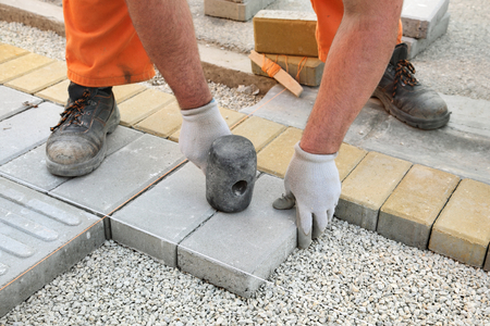Photo for Construction site, worker installing concrete brick pavement, using hammer - Royalty Free Image