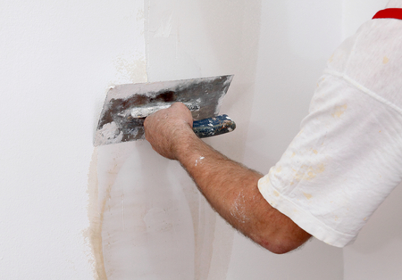 Photo for Worker spreading  plaster to wall with trowel, repairing works - Royalty Free Image