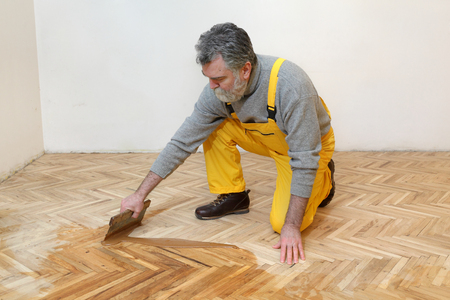 Foto de Varnishing of oak parquet floor, mature adult worker using tool - Imagen libre de derechos