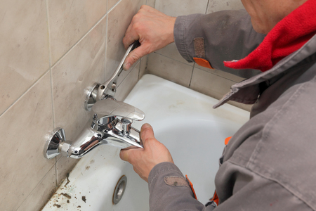 Photo pour Plumber  fixing water  tap in a bathroom using spanner - image libre de droit