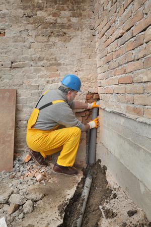 Foto de Home renovation, plumber fixing sewerage pipe at construction site - Imagen libre de derechos