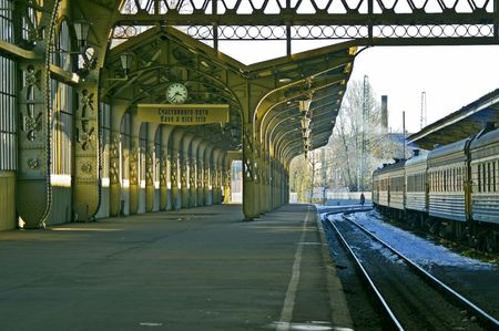 Railroad station platform with a hanging clock and \