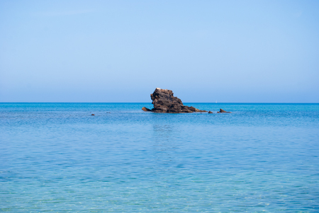Photo pour Rock surfacing from the crystalline sea with line of horizon - image libre de droit