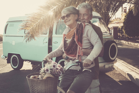 Photo for two senior aged couple go bike together in traveler vacation activities. playing and live a funny lifestyle. sun in backlight and old vintage van. - Royalty Free Image