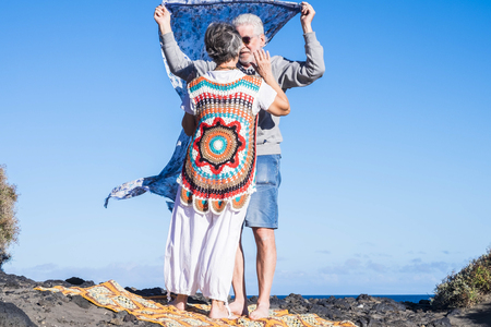 Photo for man and woman senior mature people in sweetness and carefree on the ocean coast. vacation or new life retired concept. colorful clothes and scenic place. love and life forever together - Royalty Free Image