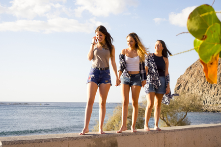 Photo for Three young women friends walk together on a wall near the beach in Tenerife. Enjoy the vacation under a blue sky with yellow sun. Hands by hands. - Royalty Free Image