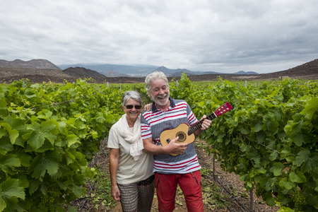 Photo for nice beautiful adult couple white hair walk on the fields of wine playing an ukulele guitar. happiness together forever with nice and craziness concept. lifestyle different for retired - Royalty Free Image
