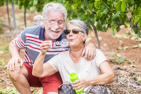 Photo for beautiful caucasian mature couple man and woman do soap bubbles together to play and have fun with joy, outdoor nature location for happy leisure activity for retired people with lifestyle - Royalty Free Image