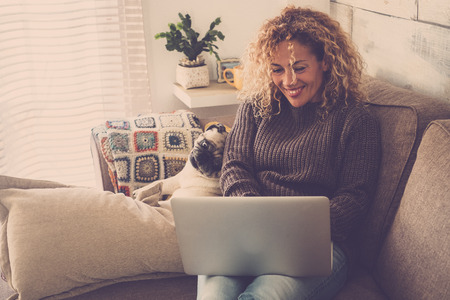 Foto de beautiful blonde curly woman working at home with a laptop internet connected while her best friends creamy pug look at the screen to check the work - friendship and lovely puppy concept - Imagen libre de derechos
