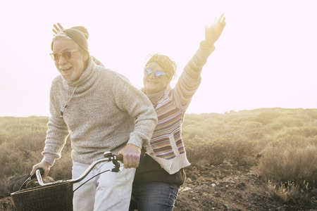 Foto de Happiness and freedom concept no limit age with old aged couple laughing smiling and having lot of fun together on a bike in outdoor leisure activity - youthful and playful people retired - Imagen libre de derechos