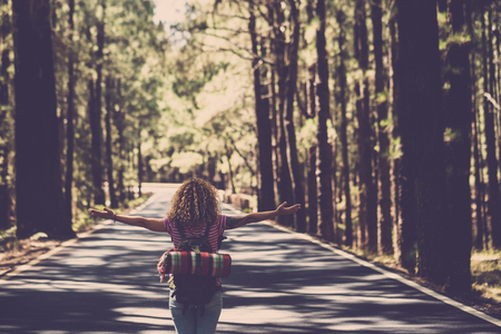 Photo pour Eternity and success satisfaction life concept with lonely girl curly hai rin the middle of long road in the forest with open arms and backpack - wanderlust and travel style people - image libre de droit