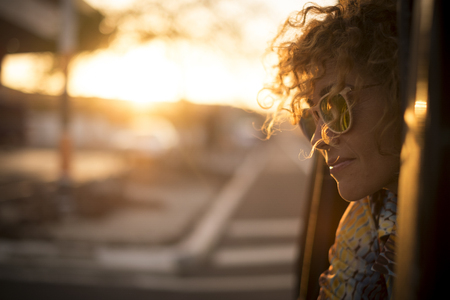 Photo for Beautiful sunny sunset time portrait for cute lady smiling and enjoying the feeling with the freedom outdoor - curly hair in the wind and sunglasses for travel concept image - Royalty Free Image