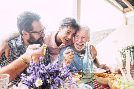 Foto de Happy people family concept laugh and have fun together with three different generations ages : grandfather father and young teenager son all together eating at lunch - Imagen libre de derechos