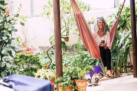 Foto de Cheerful smiling diversity people concept with beautiful trendy adult woman with white long hair laughing sit down on an hammock at home in the garden drinking a tea - Imagen libre de derechos
