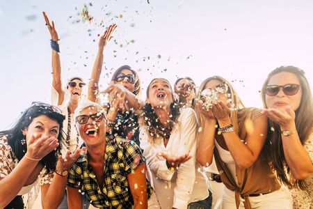 Foto de People having fun in party celebration friends concept - group of young and adult women all together laughing blowing coloured confetti - friendship and love for lifestyle with mixed active generations - Imagen libre de derechos