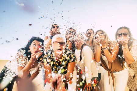 Foto de Confetti party celebration for happy cheerful crazy caucasian people women blowing out enjoying the event outdoor - carnival or birthday concept for cheerful pretty ladies - Imagen libre de derechos
