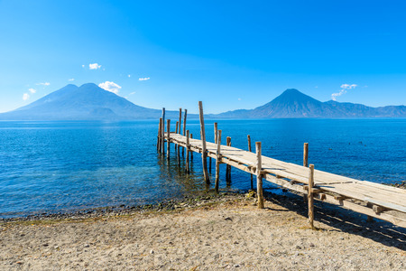 Foto per Wooden pier at Lake Atitlan on the beach in Panajachel, Guatemala.  With beautiful landscape scenery of volcanoes Toliman, Atitlan and San Pedro in the background. - Immagine Royalty Free